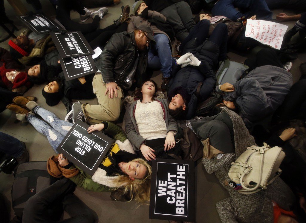 "Protesters rallying against a grand jury's decision not to indict the police officer involved in the death of Eric Garner stage a ""die-in"" at the Apple Store on Fifth Avenue, Friday, Dec. 5, 2014, in New York. (AP Photo/Jason DeCrow)"