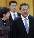 Chinese Foreign Minister Wang Yi, right, chats with a delegate as they attend a welcome ceremony for visiting Thailand Prime Minister Prayuth Chan-ocha at the Great Hall of the People in Beijing, China Monday, Dec. 22, 2014. China told the U.S. that it is against cyberattacks and opposes any nation or individual launching such attacks from a third country, but did not directly condemn the Sony hackings that Washington has blamed on North Korea, China's foreign ministry said Monday. (AP Photo/Andy Wong)