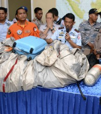Commander of Indonesian Air Force 1st Operational Command Rear Marshall Dwi Putranto, center, shows the airplane parts and a suitcase found floating on the water near the site where AirAsia flight QZ 8501 disappeared, during a press conference at the airbase in Pangkalan Bun, Central Borneo, Indonesia, Tuesday, Dec. 30, 2014. Bodies and debris seen floating in Indonesian waters Tuesday, painfully ending the mystery of AirAsia Flight QZ8501, which crashed into the Java Sea and was lost to searchers for more than two days. (AP Photo/Dewi Nurcahyani)