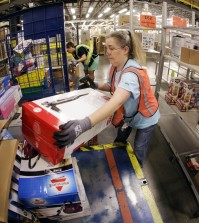 Teresa Clark fills an order at the Amazon fulfillment center in Lebanon, Tenn. on Monday, Dec. 1, 2014. Retailers rolled out discounts and free shipping deals on Cyber Monday, with millions of Americans expected to log on and shop on their work computers, laptops and tablets after the busy holiday shopping weekend. (AP Photo/Mark Humphrey)