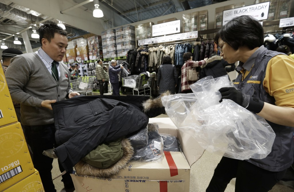 In this Nov. 28, 2014 photo,  a customer picks up to buy a down jacket directly purchased from overseas online markets at E.mart Traders in Yongin, South Korea.  The volume of goods ordered by Korean shoppers from websites overseas has surged in recent years and sales are forecast to set a record high this year above $1 billion. It remains small compared with retail sales within South Korea, which are forecast at $243 billion this year, but is expanding at a faster rate.   (AP Photo/Ahn Young-joon)