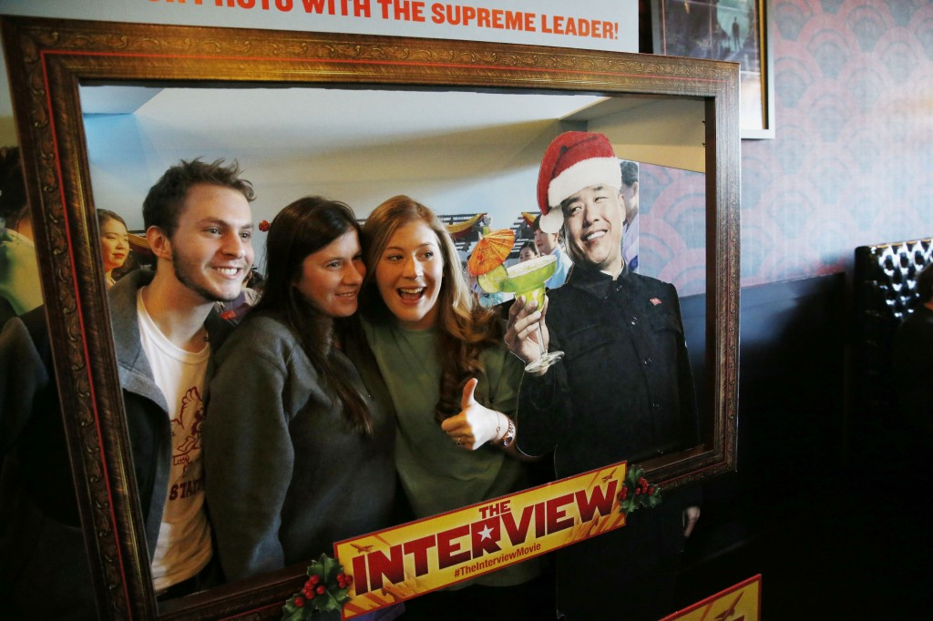 "Christmas Day moviegoers take a photograph with an advertisement for the film ""The Interview"" that is playing at the Alamo Drafthouse Cinema in Richardson, Texas, Thursday, Dec. 25, 2014. The film's Christmas Day release was canceled by Sony after threats of violence by hackers linked to North Korea, but the release was reinstated in some independent theaters and through a variety of digital platforms. (AP Photo/The Dallas Morning News, Andy Jacobsohn)"