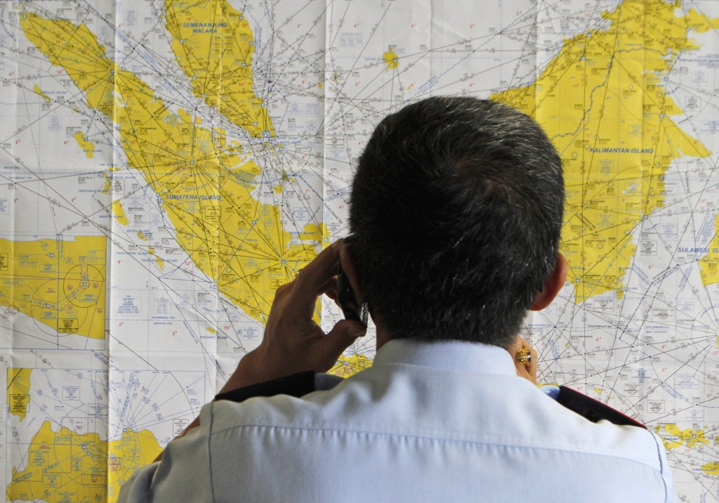 An airport official checks a map of Indonesia at the crisis center set up by local authority for the missing AirAsia flight QZ8501, at Juanda International Airport in Surabaya, East Java, Indonesia, Sunday, Dec. 28, 2014. The AirAsia plane with over 160 people on board lost contact with ground control on Sunday while flying over the Java Sea after taking off from the provincial city in Indonesia for Singapore. (AP Photo/Trisnadi)