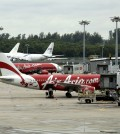 An AirAsia plane taxis, while another is parked on the tarmac at the Changi International Airport on Monday, Dec. 29, 2014 in Singapore. Search planes and ships from several countries on Monday were scouring Indonesian waters over which an AirAsia jet disappeared, more than a day into the region's latest aviation mystery. AirAsia Flight 8501 vanished Sunday in airspace thick with storm clouds on its way from Surabaya, Indonesia, to Singapore. (AP Photo/Wong Maye-E)