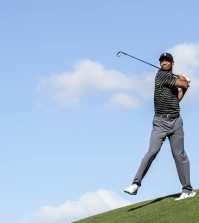 Tiger Woods chips the ball with an awkward follow through on the seventh hole during the first round of the Hero World Challenge golf tournament on Thursday, Dec. 4, 2014, in Windermere, Fla. (AP Photo/Willie J. Allen Jr.)