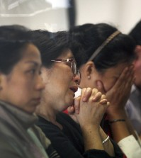 Relatives and next-of-kin of passengers on the AirAsia flight QZ8501wait for the latest news on the search of the missing jetliner at Juanda International Airport in Surabaya, East Java, Indonesia, Monday, Dec. 29, 2014. Search planes and ships from several countries on Monday were scouring Indonesian waters over which an AirAsia jet disappeared, more than a day into the region's latest aviation mystery. AirAsia Flight 8501 vanished Sunday in airspace thick with storm clouds on its way from Surabaya, Indonesia, to Singapore. (AP Photo/Trisnadi Marjan)