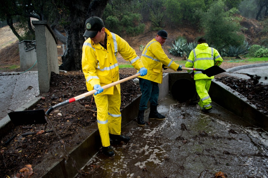 Municipal work crews clear debris and mudflows in the storm drain below the Colby Fire burn area in 1000 block of N Lorain Avenue in Glendora, Calif. on Tuesday, Dec. 2, 2014. Heavy rain from a powerful Pacific storm swept through California on Tuesday, providing some relief from a three-year drought. (AP Photo/San Gabriel Valley Tribune, Watchara Phomicinda)