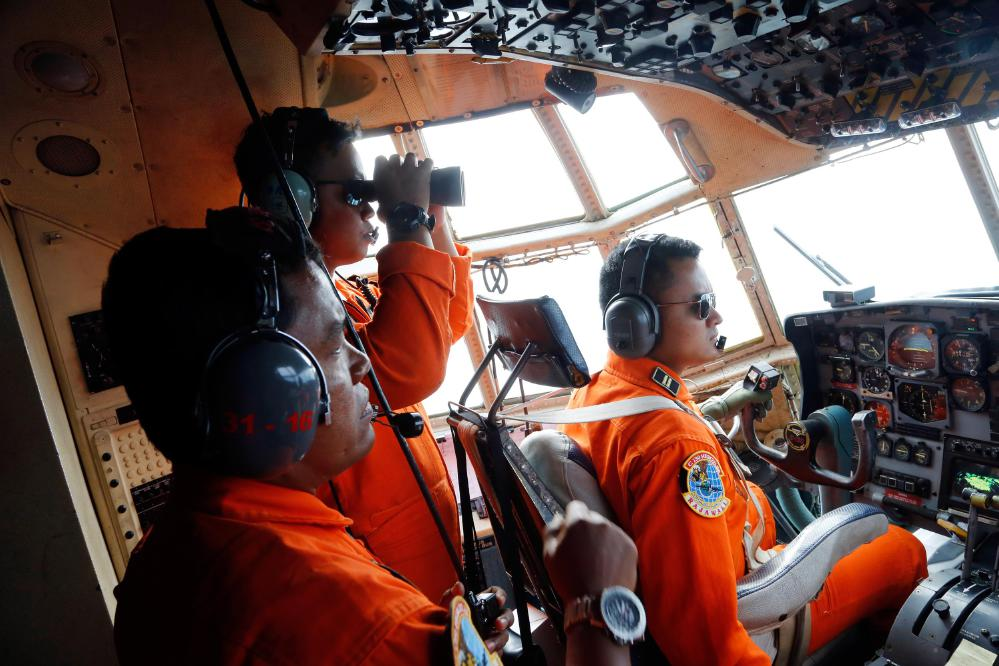 Crew of Indonesian Air Force C-130 airplane of the 31st Air Squadron scan the horizon during a search operation for the missing AirAsia flight 8501 jetliner over the waters of Karimata Strait in Indonesia, Monday, Dec. 29, 2014. Search planes and ships from several countries on Monday were scouring Indonesian waters over which the AirAsia jet disappeared, more than a day into the region's latest aviation mystery. Flight 8501 vanished Sunday in airspace thick with storm clouds on its way from Surabaya, Indonesia, to Singapore. (AP Photo/Dita Alangkara)