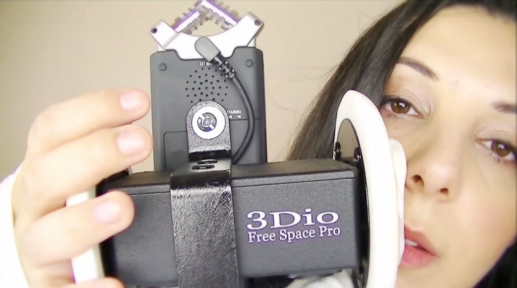ASMRtist Heather Feather, one of the most popular in the genre at 184,000 YouTube subscribers, is shown here using a specialized binaural microphone, which allows viewers to feel as if she is in the room with them. (YouTube screen capture)