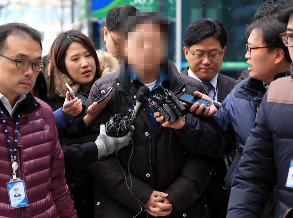 The 53-year-old professor at Seoul National University (C) is questioned by reporters before attending a prosecution probe into sexual abuse charges on Dec. 3, 2014. (Yonhap)