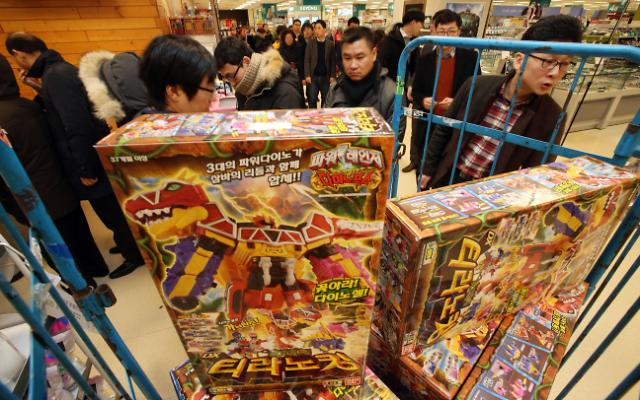 Parents line up at a Seoul supermarket on Dec. 18, 2014, to purchase the much sought-after action figures from the Power Ranger Dino Force series for their children ahead of the Christmas holiday. (Yonhap)