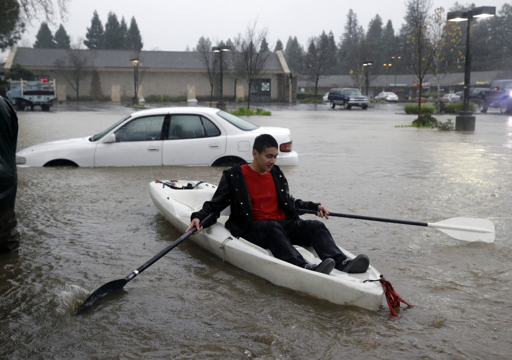 A man uses a kayak to make his way around a flooded parking lot at a shopping center Thursday, Dec. 11, 2014, in Healdsburg, Calif.  A powerful storm churned through Northern California Thursday, knocking out power to tens of thousands and delaying commuters while soaking the region with much-needed rain. (AP Photo/Eric Risberg)