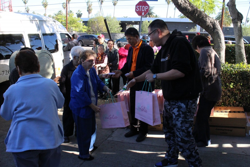 A Korean organization hands out bags filled with necessities at a senior home Tuesday in Los Angeles' Koreatown.