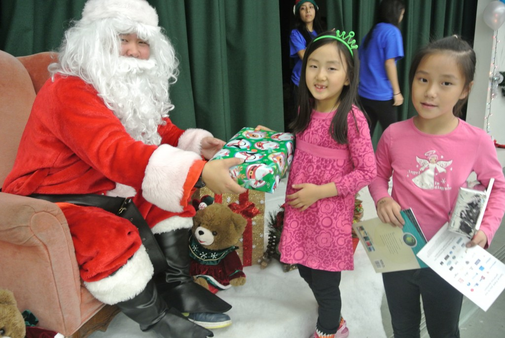 Children receive gifts from Santa at KYCC's carnival Saturday. (Park Ji-hye/The Korea Times)