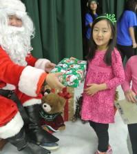 Children receive gifts from Santa at KYCC's carnival Saturday. (Park Ji-hye/The Korea Times)