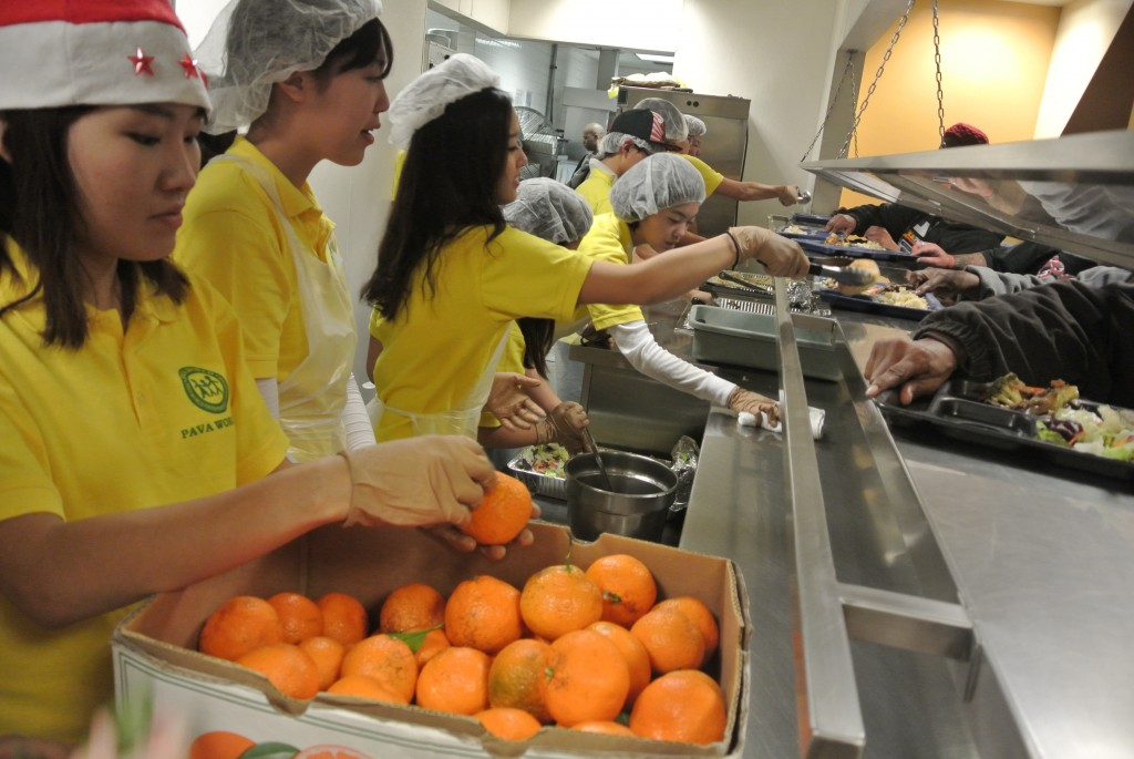 PAVA World student volunteers give out food to the homeless at Midnight Mission Saturday. (Park Ji-hye/The Korea Times)