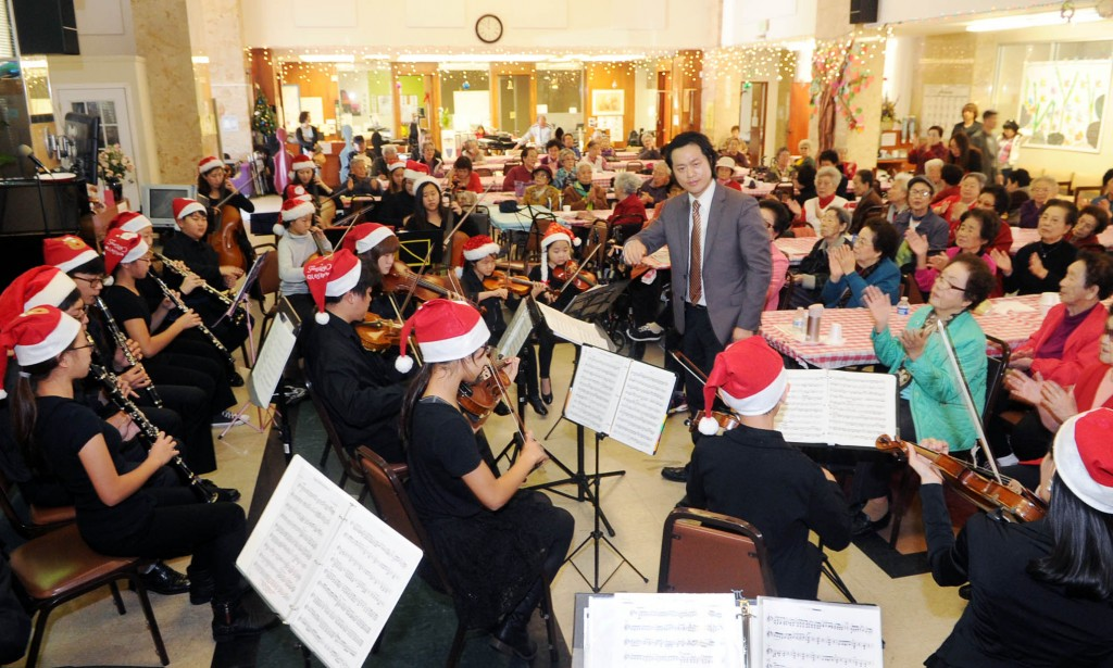 Hayfield Youth Orchestra, led by conductor KIm Yong-jae, performs at Wilshire Day Care Center Monday. (Park Sang-hyuk/The Korea Times)