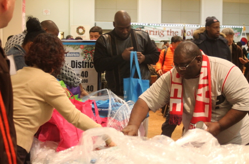 Local residents receive food baskets at the 5th Sharing the Holiday Spirit Food Drive by Chade Foundation and Bees Sales Company Saturday.
