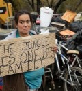 Yolanda Gutierrez, a 2-year resident of a homeless encampment known as The Jungle, holds a sign in protest Thursday, Dec. 4, 2014, in San Jose, Calif. (Marcio Jose Sanchez/AP)