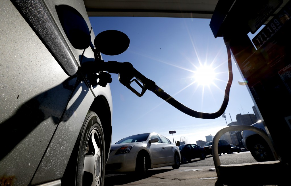 Vehicles form a line behind a motorist gassing up at a gas station where the cash price for regular unleaded is listed at $1.71, Friday, Jan. 23, 2015, in Newark, N.J. For the first time since 2009, most Americans are paying less than $2 a gallon. (AP Photo/Julio Cortez)