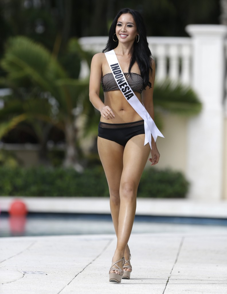Miss Universe contestant Elvira Devinamira, of Indonesia, walks along the pool during the Yamamay swimsuit runway show, Wednesday, Jan. 14, 2015, in Doral, Fla. The Miss Universe pageant will be held Jan. 25 in Miami. (AP Photo/Lynne Sladky)