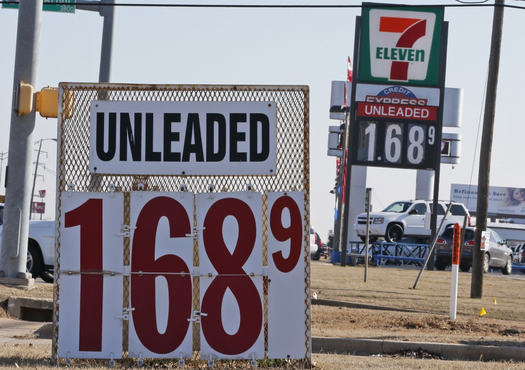 Signs at two gas stations advertise unleaded gasoline for $1.68, in Oklahoma City, Friday, Jan. 23, 2015. For the first time since 2009, most Americans are paying less than $2 a gallon. (AP Photo/Sue Ogrocki)