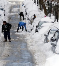 People work to shovel snow-covered cars out in Boston's Charlestown section, Wednesday, Jan. 28, 2015, one day after a blizzard dumped about two feet of snow in the city. (AP Photo/Elise Amendola)
