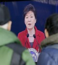 People watch a live television program airing South Korean President Park Geun-hye's New Year's press conference at the Seoul Railway Station in Seoul, Monday, an. 12, 2015. (AP Photo/Lee Jin-man)