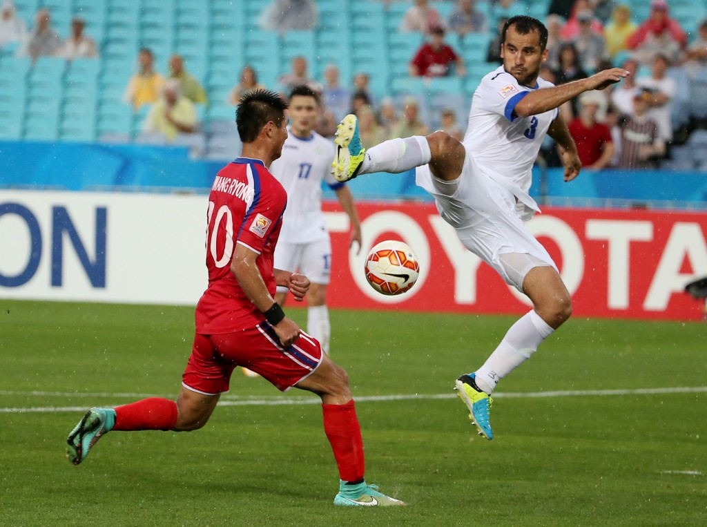Uzbekistan's Shavkatjon Mulladjanov kicks the ball as North Korea's Pak Kwang Ryong attempts to block during the first round soccer match of the AFC Asia Cup between Uzbekistan and North Korea in Sydney, Australia,  Saturday, Jan. 10, 2015. (AP Photo/Rob Griffith)