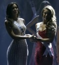 Paulina Vega of Colombia, left, and Nia Sanchez of the U.S., hold hands as the wait for the announcement of who will be selected as Miss Universe, Sunday, Jan. 25, 2015, during the Miss Universe pageant in Miami. (AP Photo/Wilfredo Lee)