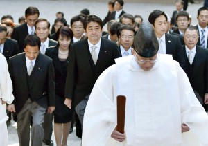 Japan's Prime Minister Shinzo Abe, center, and his cabinet ministers, escorted by a Shinto priest, arrive at the Grand Shrine of Ise, central Japan, for offering a new year's prayer Monday, Jan. 5, 2015.  Japanese Prime Minister Abe said Monday that his government would express remorse for World War II on the 70th anniversary of its end in August. (AP Photo/Kyodo News)