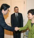 President Park Geun-hye and Japanese Prime Minister Shinzo Abe shake hands during a trilateral summit with President Barack Obama at the U.S. embassy in The Hague. (Yonhap)