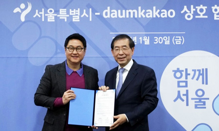 Seoul Mayor Park Won-soon, right, smiles with Daum Kakao CEO Lee Sirgoo after the KakaoTalk operator agreed with the Seoul Metropolitan Government, Friday, to offer citizens real-time information on natural disasters via the messaging application. (Courtesy of Daum Kakao)