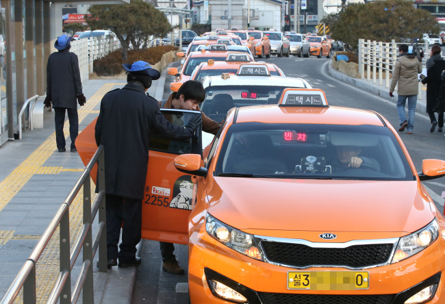 Taxies form a long queue at a taxi stop in Seoul. (Yonhap)