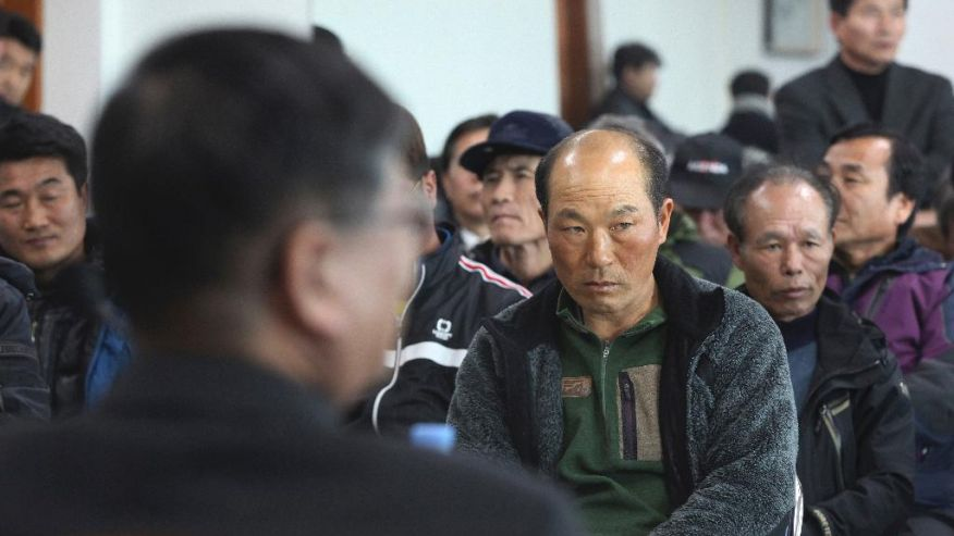 A government official, foreground, meets with salt farm owners and workers as a part of human rights inspection on Sinui Island, South Korea. Life as a salt-farm slave was so bad Kim Jong-seok sometimes fantasized about killing the owner who beat him daily. Freedom, he says, has been worse. In the year since police emancipated the severely mentally disabled man from the farm where he had worked for eight years, Kim has lived in a grim homeless shelter, preyed upon and robbed by other residents. He has no friends, no job training prospects or counseling, and feels confined and deeply bored. (AP Photo/Ahn Young-joon)