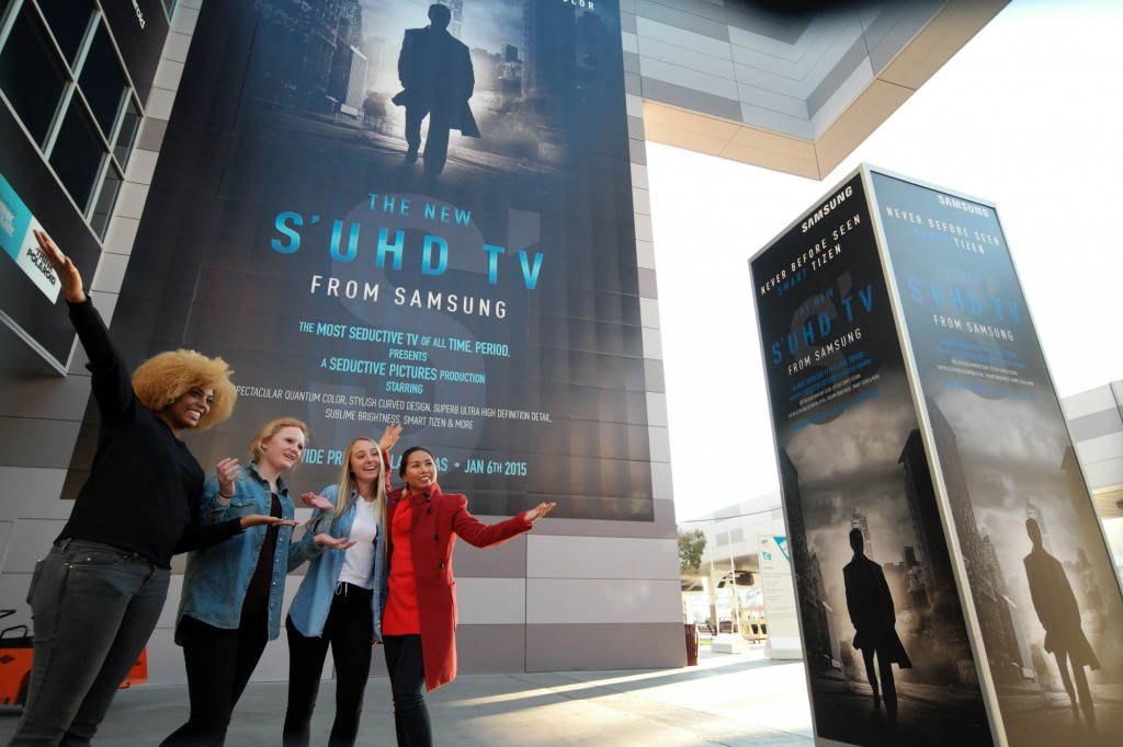 Visitors pose in front of Samsung's advertisement for its latest TV technology at the Consumer Electronics Summit in Las Vegas. (Korea Times file)