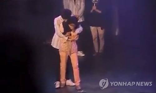 A Malaysian fan is hugged by a member of K-pop band B1A4 during a Kuala Lumpur fan event. (YouTube capture)