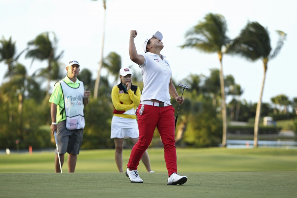 Second place finisher Sun Young Yoo of South Korea, background in yellow, watches Sei Young Kim of South Korea, pump her fist in the air after winning the Pure Silk Bahamas LPGA Classic at the Ocean Club Golf Course, in Paradise Island, Bahamas, Sunday, Feb. 8, 2015. (AP Photo/Tim Aylen)