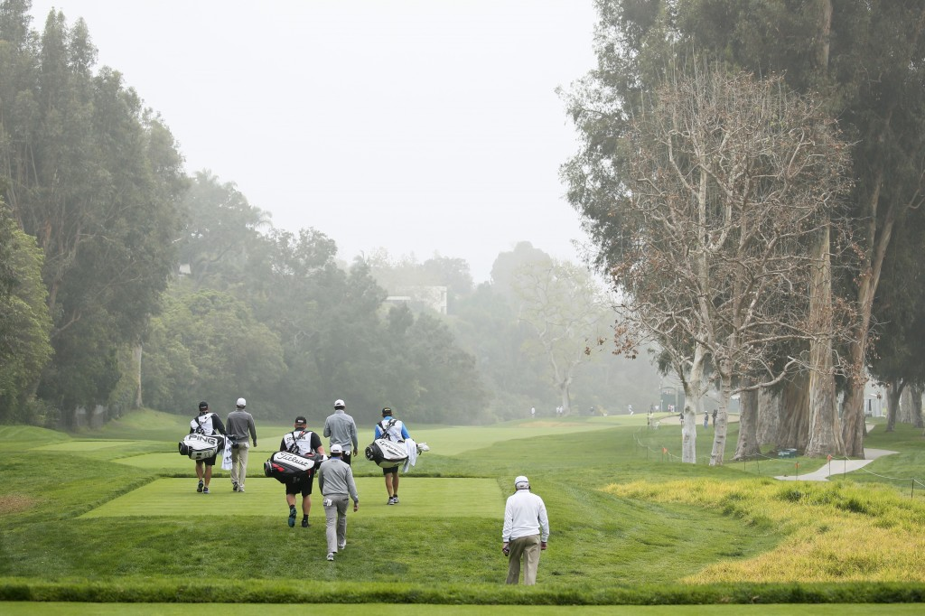 The grouping of Carlos Ortiz, left, and Erik Compton, center, and James Hahn, right, walk down the fairway after teeing off on the 12th hole during the first round of the Northern Trust Open golf tournament at Riviera Country Club in the Pacific Palisades area of Los Angeles on Thursday, Feb. 19, 2015. (AP Photo/Danny Moloshok)