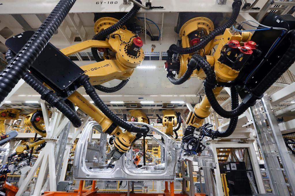 Robots install rivets on a 2015 Ford F-150 truck at the Dearborn Truck Plant in Dearborn, Mich. Cheaper, better robots will replace human workers in the world's factories at a faster pace over the next decade, pushing manufacturing labor costs down 16 percent, a report from the Boston Consulting Group said Tuesday, Feb. 10, 2015. (AP Photo/Paul Sancya)