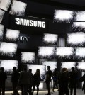 Attendees watch a presentation at the Samsung booth at the International CES, Thursday, Jan. 8, 2015, in Las Vegas. (AP Photo/Jae C. Hong)