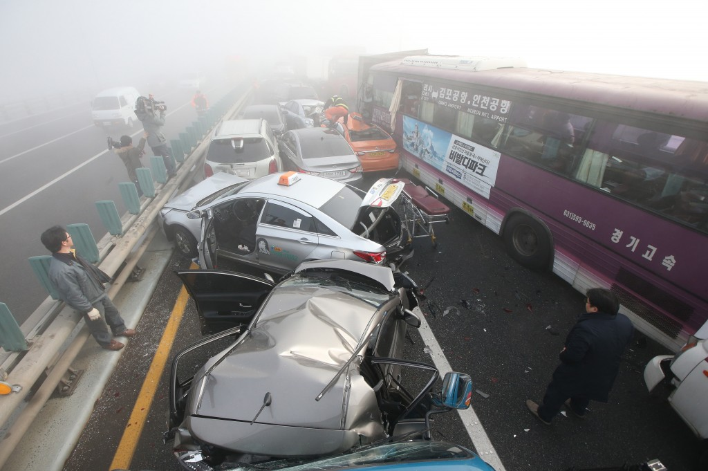 Damaged vehicles sit on Yeongjong Bridge in Incheon, South Korea, Wednesday, Feb. 11, 2015. Two people were killed and at least 42 were injured on Wednesday after a pileup involving about 100 vehicles in foggy weather on the bridge near the Incheon International Airport, South Korean officials said.(AP Photo/Yonhap, Suh Myung-gon)