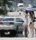 Citizens walk on a road in Yeouido, central Seoul, on Aug. 1, 2014, after the first heat wave warning of this year was issued in the capital area. The warning is usually issued if the daily high temperature is expected to rise above 35 C for two days in a row. (Yonhap)