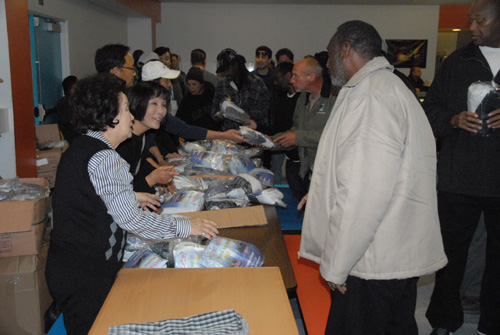 JABI Charity Association volunteers hand out underwear sets to the homeless at Cityteam.
