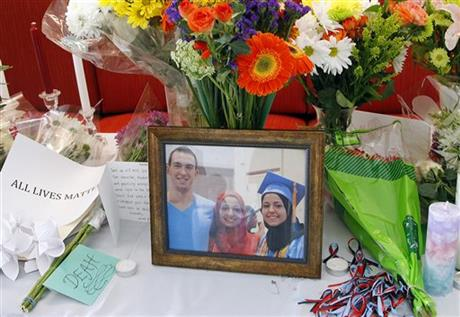A makeshift memorial appears on display, Wednesday, Feb. 11, 2015, at the University of North Carolina School of Dentistry in Chapel Hill, N.C., in remembrance of Deah Shaddy Barakat, 23, Yusor Mohammad, 21, and Razan Mohammad Abu-Salha, 19, who were killed on Tuesday. Craig Stephen Hicks, 46, has been charged with three counts of first-degree murder in the case. (AP Photo/The News & Observer, Chris Seward)