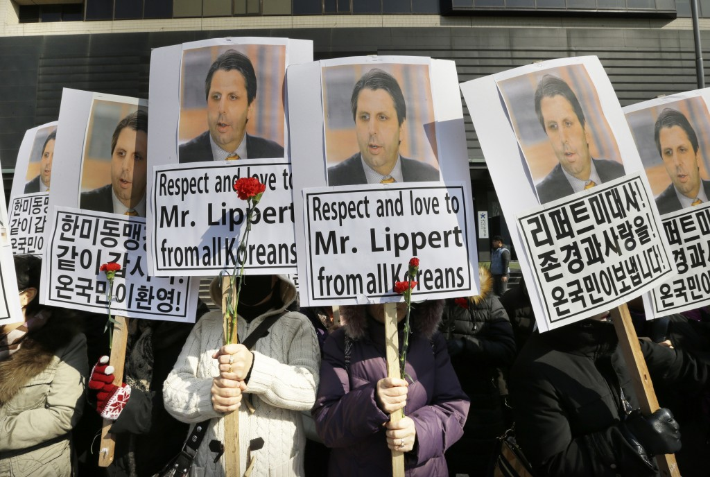 "South Korean conservative activists hold portraits of U.S. Ambassador to South Korea Mark Lippert during a rally demanding his  speedy recovery near the U.S. embassy in Seoul, South Korea, Friday, March 6, 2015. A knife attack Thursday that injured Lippert is the latest act of political violence in a deeply divided country where some protesters portray their causes as matters of life and death.  The letters read "" We love U.S. Ambassador to South Korea Mark Lippert  and demand the alliance between South Korea and the United States"" (AP Photo/Ahn Young-joon)"