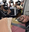 A suspect, identified by police as 55-year-old Kim Ki-jong, is carried on a stretcher off an ambulance as he arrives at a hospital in Seoul, South Korea, Thursday, March 5, 2015. Lippert was in stable condition after a man screaming demands for a unified North and South Korea slashed him on the face and wrist with a knife, South Korean police and U.S. officials said Thursday.(AP Photo/Yonhap, Han Jong-chan)