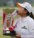 Park Inbee of South Korea kisses the trophy when prompted by organizers as she celebrates after winning the HSBC Women's Champions golf tournament on Sunday, March 8, 2015 in Singapore. (AP Photo/Wong Maye-E)