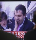 South Korean men watch a TV news program reporting U.S. Ambassador to South Korea Mark Lippert injured in a knife attack at Seoul railway station in Seoul, South Korea, Thursday, March 5, 2015. Lippert was slashed on the face and wrist by a man wielding a weapon with a 10-inch blade and screaming that the rival Koreas should be unified, South Korean police said. (AP Photo/Ahn Young-joon)