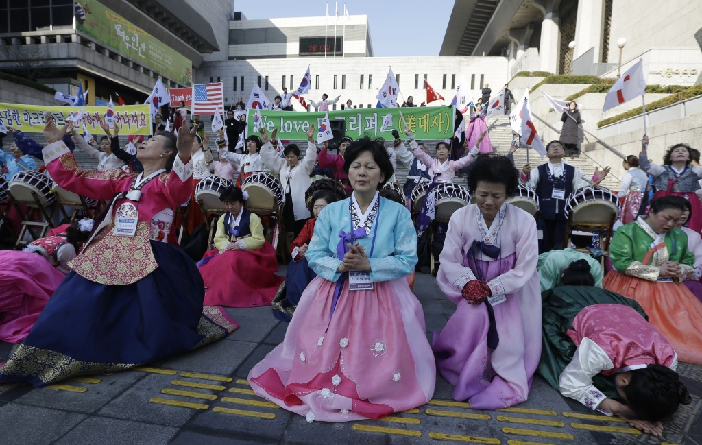 South Korean Christian women pray for the speedy recovery of U.S. Ambassador to South Korea Mark Lippert, during a gathering near the U.S. embassy in Seoul, South Korea, Saturday, March 7, 2015.  Police on Friday investigated the motive of the anti-U.S. activist they say slashed the U.S. ambassador to South Korea, as questions turned to whether security was neglected. (AP Photo/Ahn Young-joon)